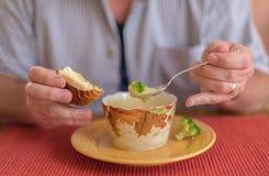 Fleisch fressende Brokkolicheddarkäsesuppe für das Mittagessen Lizenzfreies Stockbild