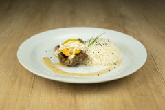 Fleisch mit Pfirsichen und Reis auf Platte auf Holztisch stockbild
