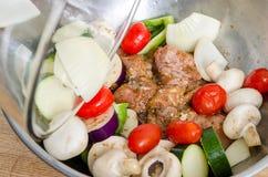 Fleisch und Gemüse mariniert in der Schüssel auf Holzoberfläche Lizenzfreies Stockbild