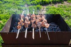 Fleisch wird auf Aufsteckspindeln auf dem Grill gebraten Stockfotos