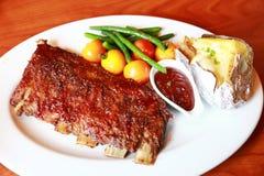 Fleisch wohlschmeckend auf Tabelle: braten Sie Schulter mit Tomate und Schnittlauchen über weißer Platte Lizenzfreie Stockfotos