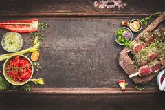 Fleischaufsteckspindeln mit Gemüse und frischer Würze, Vorbereitung für Grill oder BBQ auf dunklem Weinlesehintergrund, Draufsich Stockbilder
