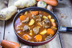 Fleischeintopfgericht mit Gemüse auf rustikalem hölzernem Hintergrund Stockfotografie