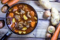 Fleischeintopfgericht mit Gemüse auf rustikalem hölzernem Hintergrund Stockfotos