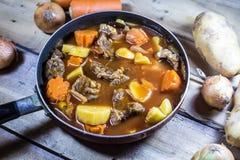 Fleischeintopfgericht mit Gemüse auf rustikalem hölzernem Hintergrund Stockbilder