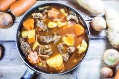 Fleischeintopfgericht mit Gemüse auf rustikalem hölzernem Hintergrund Lizenzfreie Stockbilder