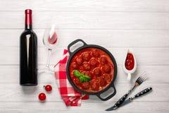 Fleischklöschen in der Tomatensauce in einer Bratpfanne mit Flasche des Weins, zwei Gläser, des Messers und der Gabel auf einem w lizenzfreies stockbild