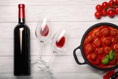 Fleischklöschen in der Tomatensauce in einer Bratpfanne mit Kirsche, Tomaten, Flasche Wein und zwei Gläsern auf einem weißen hölz stockbild