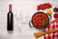Fleischklöschen in der Tomatensauce in einer Bratpfanne mit Kirsche, Tomaten, Flasche Wein und zwei Gläsern auf einem weißen hölz stockfotos