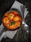 Fleischklöschen in der Tomatensauce, in einer Gabel und in einem Löffel auf einem hölzernen Hintergrund Stockfotografie
