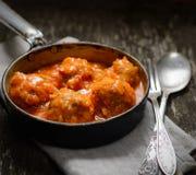Fleischklöschen in der Tomatensauce, in einer Gabel und in einem Löffel auf einem hölzernen Hintergrund Lizenzfreies Stockfoto