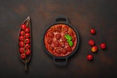 Fleischklöschen in der Tomatensauce mit Gewürzen, Kirschtomaten, Teigwaren und Basilikum in einer Bratpfanne auf rostigem braunem lizenzfreies stockbild