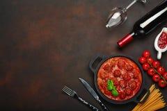 Fleischklöschen in der Tomatensauce mit Gewürzen, Kirschtomaten, Teigwaren und Basilikum in einer Bratpfanne mit Flasche des Wein stockfotos