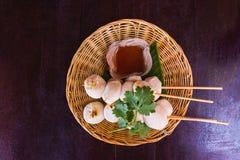 Fleischklöschen rösteten auf hölzernem Korbteller und eine Schale Soße verziert mit Koriander setzte auf dem Tisch dunkles Holz B lizenzfreie stockbilder