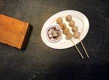 Fleischklöschen und würzige Soße im weißen Teller auf der schwarzen Tischplatteansicht lizenzfreies stockbild