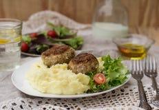 Fleischklöschenkoteletts mit Kartoffelpürees und Salat Stockbild