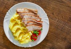 Fleischscheiben mit Kartoffelpürees in der weißen Platte auf Holztisch stockbilder