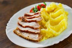 Fleischscheiben mit Kartoffelpürees in der weißen Platte auf Holztisch lizenzfreie stockfotos