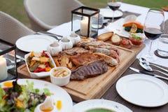 Fleischservierplatte diente mit Salat, Fischrogen mit Wahl drei der Soße auf hölzernem Block am feinen Speisetischsatz Lizenzfreies Stockbild