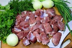 Fleischstücke auf dem rohen Schweinefleisch des Brettes Stockbilder