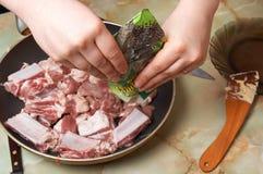 Fleischstücke in Bratpfanne legend, fügen Sie Pfeffer hinzu Lizenzfreies Stockfoto