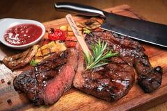 Fleischsteak auf dem hölzernen Brett mit Soße stockbilder