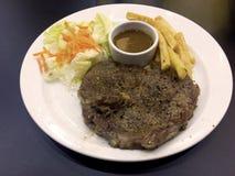 Fleischsteak des schwarzen Pfeffers mit Soßensoße, -pommes-Frites und -salat lizenzfreie stockbilder