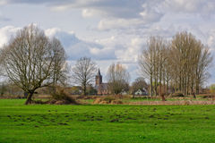 Flemish famland landscape with church. Flemish famland landscape with a meadow, bare trees and the curch of the village of Zevergem in the valley of river Stock Photos