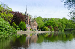 Flemish style building reflecting in Minnewater lake Stock Image