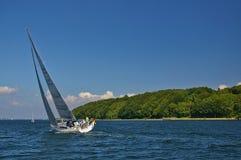 Flensburg, l'Allemagne - 31 mai 2011 - yacht moderne de navigation dans les eaux calmes gîtant avec le ciel bleu et Ne boisé vert Photographie stock libre de droits