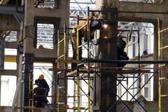 Flera arbetare och welders som förstärker pelarproduktionkorridoren Royaltyfri Bild