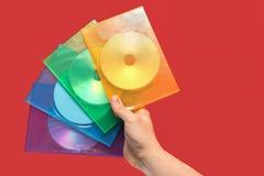 Flera askar av CD förestående med röd bakgrund Arkivbild