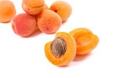 Flera av skördade aprikors som är hela och halveras på den vita backgrouen Arkivfoto