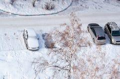 Flera bilar i gataparkering som täckas med snö efter ett snöfall ovanför sikt royaltyfria bilder