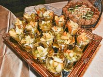 Flera efterrättexponeringsglas med fruktsallad lade på ett dekorativt magasin för spegel royaltyfri foto