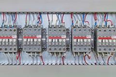 Flera elektrisk contactor på en beslagpanel i elektrisk garderob arkivfoto