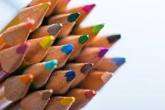 Flera färgblyertspennor på ett vitbokark Arkivbilder