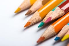 Flera färgblyertspennor på ett vitbokark Arkivfoto