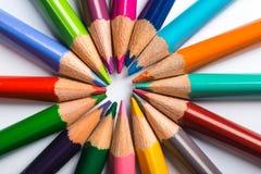 Flera färgblyertspennor på ett vitbokark Arkivbild
