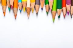 Flera färgblyertspennor på ett vitbokark Arkivfoton