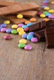 Flera färgrika chokladbesservisser på träbräde Royaltyfri Foto