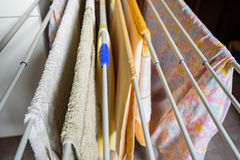 Flera färgrika handdukar torkar på uttorkninglinje inomhus Royaltyfri Foto