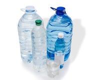 Flera flaskor och glas av vatten Arkivbilder