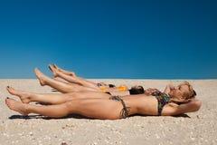 Flera flickor i bikinin som ligger på den sandiga stranden arkivbild