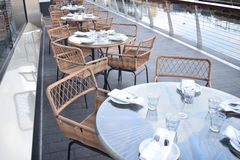 Flera glass tabeller med trästolar ordnar till förberett för lunch Fotografering för Bildbyråer