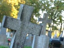 Flera gravar med granit korsar i kyrkogården, solnedgång royaltyfri bild