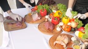 Flera händer förbereder sig för matställe i köket Bitande nya grönsaker och rått kött på en träbänk i a lager videofilmer