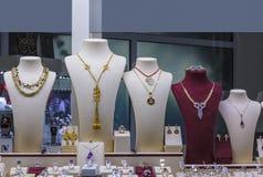 Flera halsband på smycken ställer ut i fönster royaltyfri fotografi