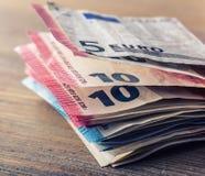 Flera hundra eurosedlar som staplas av värde Europengarbegrepp euroen bemärker reflexion bank repet för anmärkningen för pengar f Arkivbilder