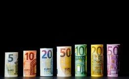 Flera hundra eurosedlar som staplas av värde Rolls eurobankn Royaltyfri Foto